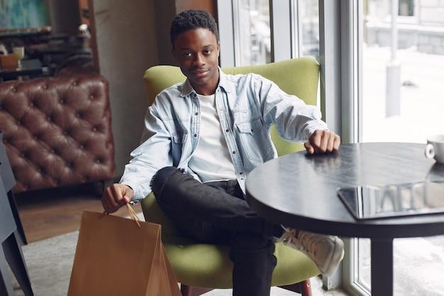 Zwarte man zit in een café en een kopje koffie drinken