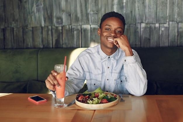 Zwarte man zit in een cafe en het eten van een groente salade