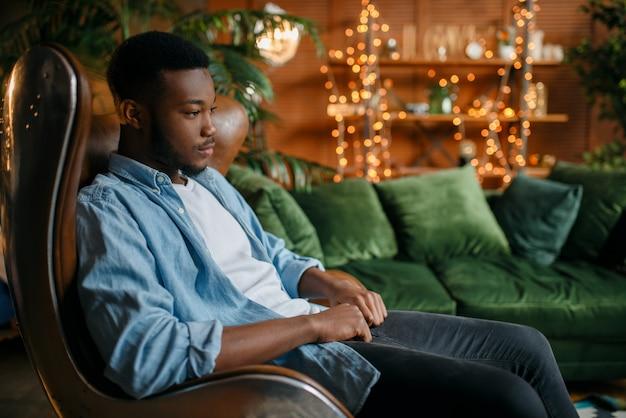 Zwarte man zit in een comfortabele leren stoel in de woonkamer, ontspanning thuis.