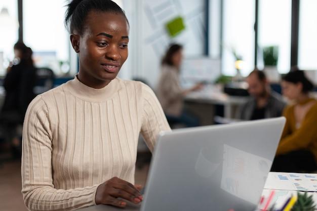 Zwarte manager leest taken op laptop en typt zittend aan een bureau in een druk opstartkantoor, terwijl een divers team statistische gegevens op de achtergrond analyseert. multi-etnische groep praten over project