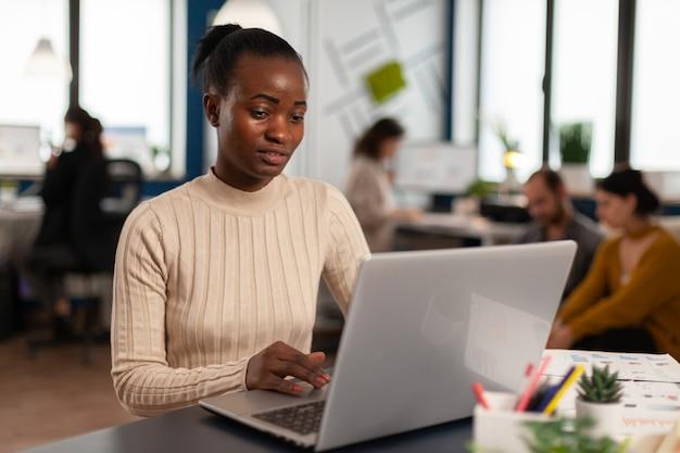 Zwarte manager leest taken op laptop en typt zittend aan een bureau in een druk opstartkantoor terwijl een divers team statistische gegevens op de achtergrond analyseert