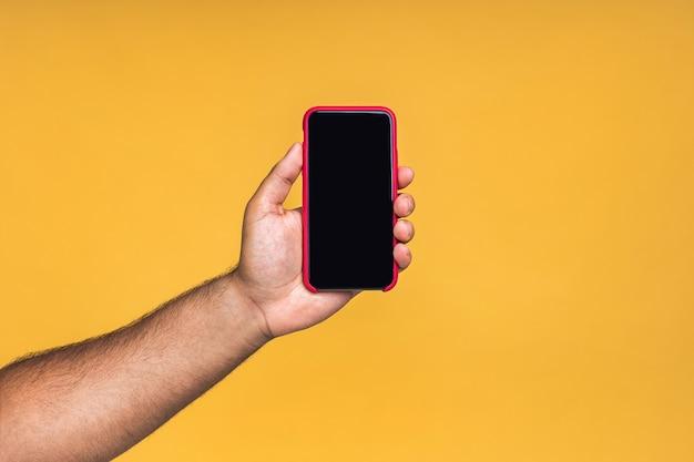 Zwarte mannelijke afro-amerikaanse indiase hand die het display van de mobiele telefoon aanraakt en met de wijsvinger naar een leeg scherm wijst, geïsoleerd op een gele achtergrond, kopieerruimte, knipsel.