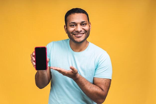 Zwarte mannelijke afro-amerikaanse indiase man die het display van de mobiele telefoon aanraakt en met de wijsvinger naar een leeg scherm wijst, geïsoleerd op gele achtergrond, kopieer ruimte, knipsel.
