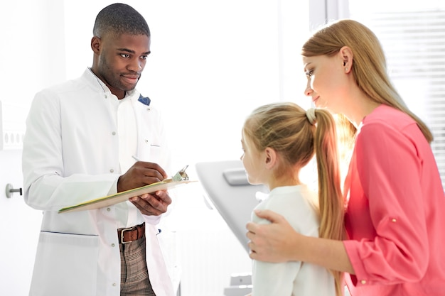 Zwarte mannelijke arts in gesprek met kind en zijn moeder tijdens gezondheidscontrole in de kliniek, moeder en meisje krijgen advies van professionele kinderarts of huisarts tijdens bezoek aan het ziekenhuis