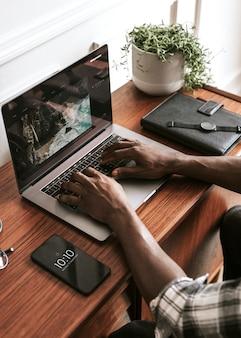 Zwarte mannelijke blogger die een laptop gebruikt