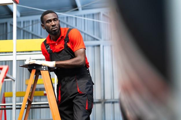 Zwarte mannelijke monteur kiest autoband bij een bandenwinkel. expertise monteur werkzaam in auto reparatie garage.