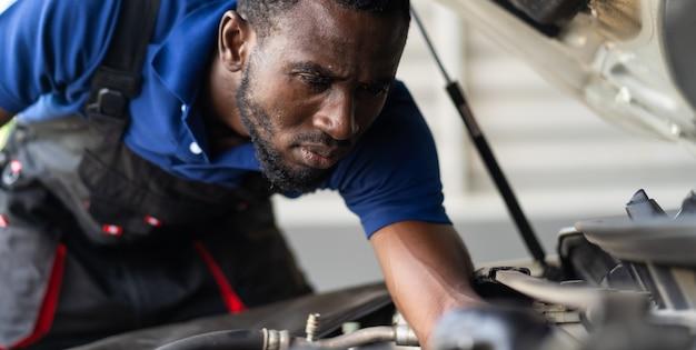 Zwarte mannelijke monteur repareert auto in garage. auto-onderhoud en auto service garage concept.