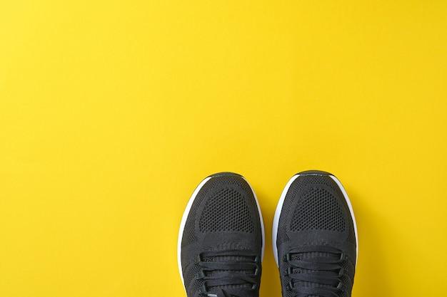 Zwarte mannen sneakers op gele achtergrond. mode blog of tijdschrift concept. herenschoenen, trendy sneakers, mode, lifestyle. bespotten. platte bovenaanzicht kopie ruimte minimale achtergrond.