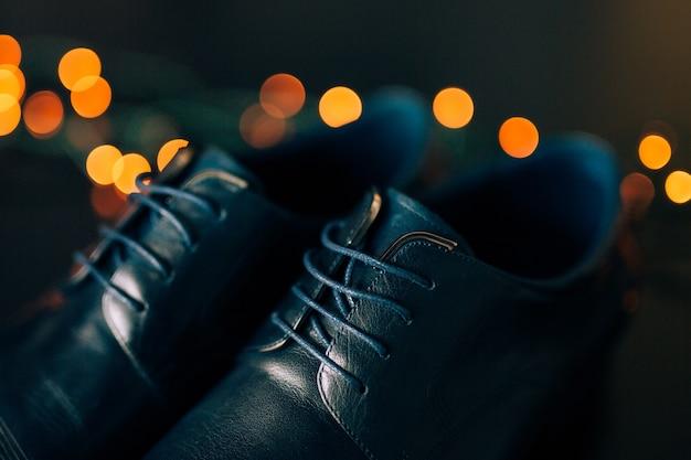 Zwarte mans schoenen met veters tegen achtergrond bokeh