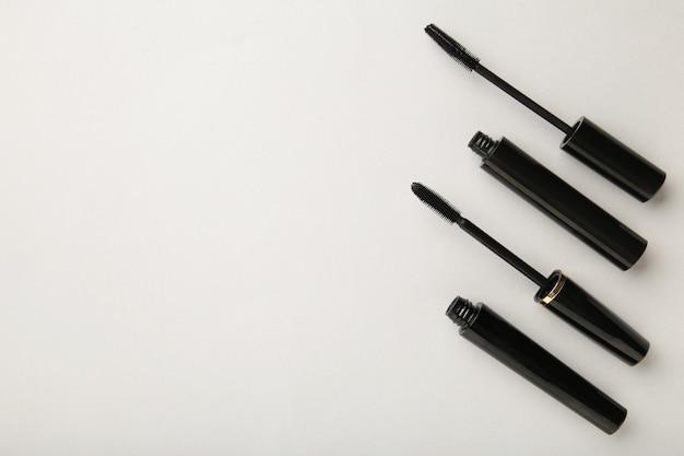 Zwarte mascara toverstaf en buis op grijze achtergrond met kopie ruimte. bovenaanzicht