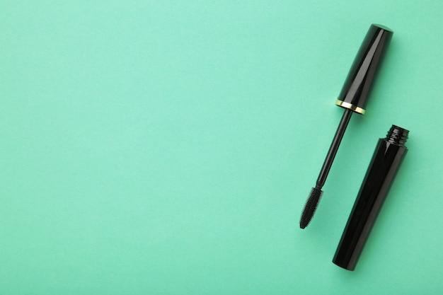 Zwarte mascara toverstaf en buis op mint achtergrond met kopie ruimte. bovenaanzicht