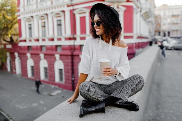 Zwarte meisjeszitting op de brug en het houden van kop van koffie of thee tijdens haar vrije tijd. freelance vrouw. het dragen van zwarte hoed en zonnebril.