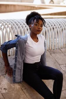 Zwarte meisjeszitting op de straat in de zomer