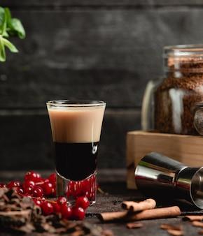 Zwarte melkachtige cocktail met bessen en kaneelstokjes.