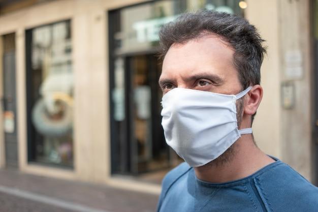 Zwarte mens die een wit masker in een stadsstraat dragen, coronavirus covid preventieconcept