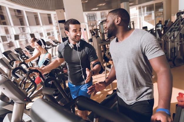 Zwarte mens die in de gymnastiek met een vriend uitoefent.