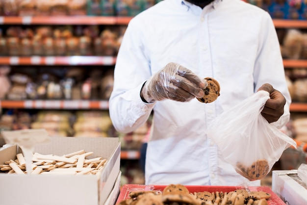 Zwarte mens die koekjes in plastic zak in kruidenierswinkel zetten