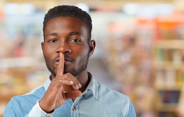 Zwarte mens die stiltegebaar met vinger op zijn lippen toont