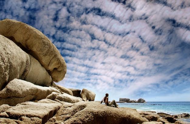 Zwarte mens gezet op overzeese rotsen die overzees kijken