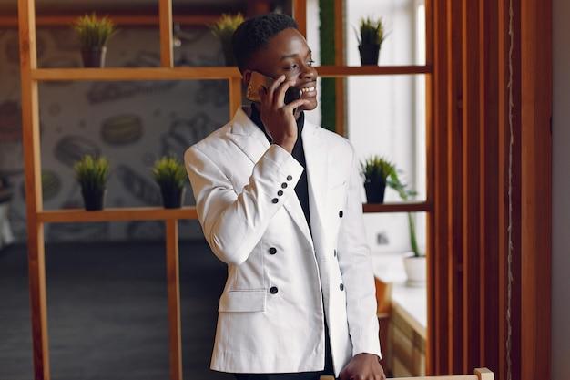 Zwarte mens in een wit jasje dat zich met een telefoon bevindt