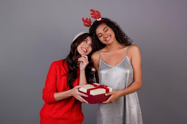 Zwarte met kaukasisch meisje die haar verrassen met giftdoos die kerstmishoed dragen die over grijs wordt geïsoleerd