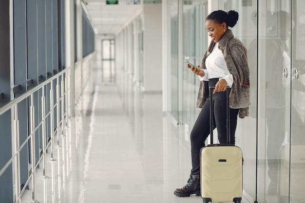 Zwarte met koffer op de luchthaven