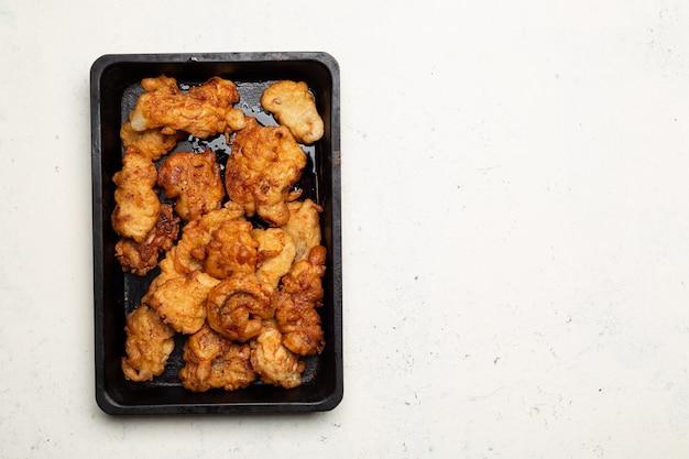 Zwarte metalen pan met gehavende vis of kip of vlees