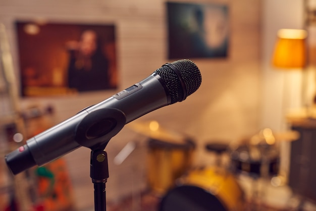 Zwarte microfoon tegen posters van populaire moderne vrouwelijke muzikanten