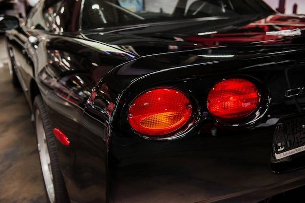 Zwarte moderne auto met lichten binnenshuis geparkeerd op autoshow