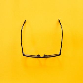 Zwarte moderne oogglazen op geel.