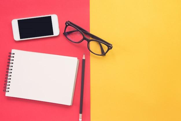 Zwarte moderne oogglazen, smartphone en leeg notitieboekje op rood en geel.