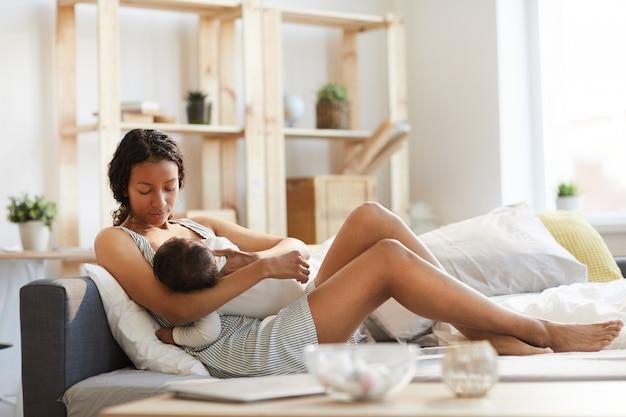 Zwarte moeder die baby borstvoeding geeft