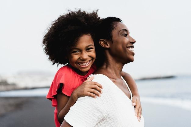 Zwarte moeder en dochter samen plezier buiten tijdens zomervakantie - focus op meisje gezicht