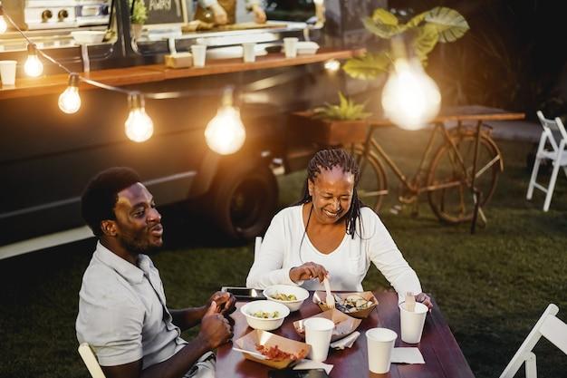 Zwarte moeder en zoon eten en drinken gezond voedsel in het restaurant van de foodtruck buiten - focus op het gezicht van een oudere vrouw