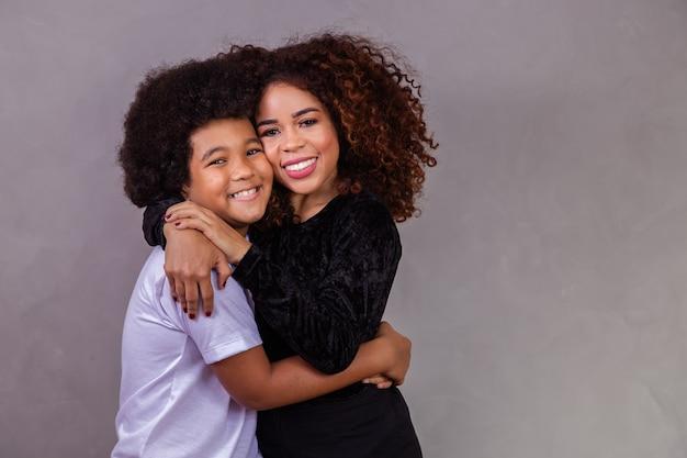 Zwarte moeder en zoon knuffelen op grijze achtergrond