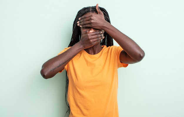 Zwarte mooie vrouw die gezicht bedekt met beide handen en nee zegt tegen de camera! foto's weigeren of foto's verbieden