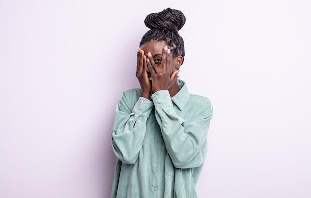 Zwarte mooie vrouw die haar gezicht bedekt met handen, tussen de vingers gluurt met een verbaasde uitdrukking en naar de zijkant kijkt