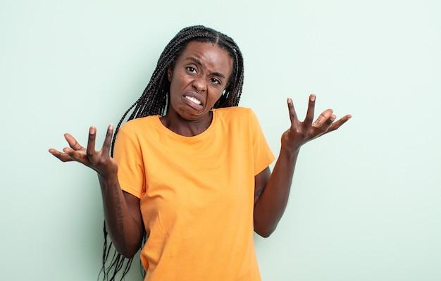 Zwarte mooie vrouw die haar schouders ophaalt met een domme, gekke, verwarde, verbaasde uitdrukking, geïrriteerd en geen idee