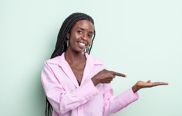 Zwarte mooie vrouw die lacht, zich gelukkig, zorgeloos en tevreden voelt, wijzend naar concept of idee op kopieerruimte aan de zijkant