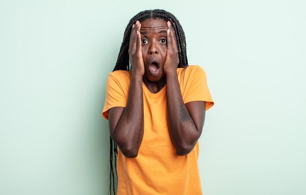 Zwarte mooie vrouw die onaangenaam geschokt, bang of bezorgd kijkt, mond wijd open en beide oren met handen bedekt