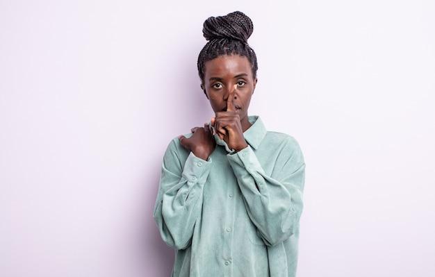 Zwarte mooie vrouw die serieus kijkt en kruist met de vinger tegen de lippen gedrukt die stilte of stilte eist en een geheim bewaart