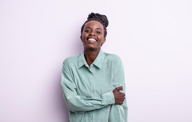 Zwarte mooie vrouw die verlegen en opgewekt lacht, met een vriendelijke en positieve maar onzekere houding