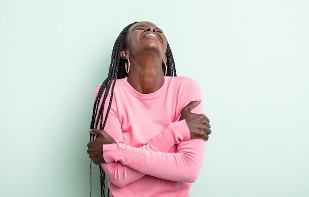 Zwarte mooie vrouw die vrolijk lacht met gekruiste armen, met een ontspannen, positieve en tevreden pose