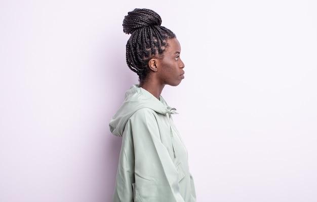 Zwarte mooie vrouw in profielweergave die ruimte vooruit wil kopiëren, denken, fantaseren of dagdromen