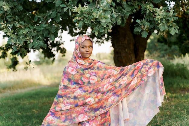 Zwarte moslimvrouw afrikaanse etniciteit weared traditionele kleurrijke hijab glimlacht onder groene boom