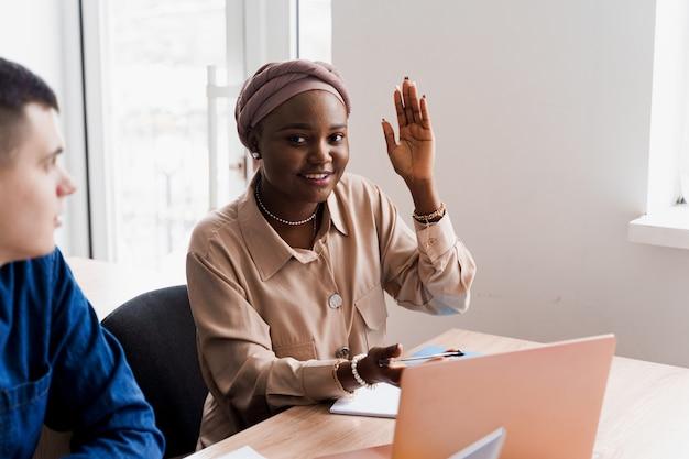 Zwarte moslimvrouw steekt haar hand op en stelt de vraag van de leraar. privéstudie op een buitenlandse school met een schoolvrouw. leraar legt grammatica van moedertaal uit met behulp van laptop. voorbereiding op examen met tutor.