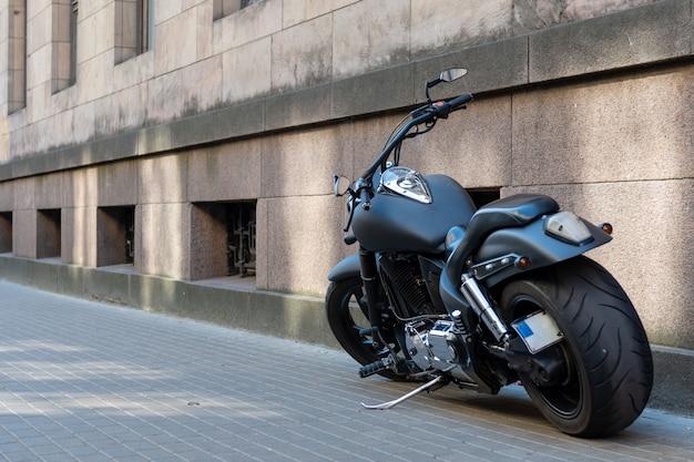 Zwarte motorfiets met grote banden op de stoep.