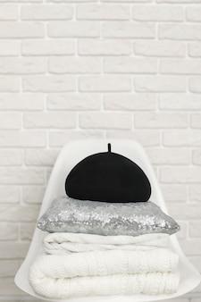 Zwarte muts, kussen en gebreide deken op stoel