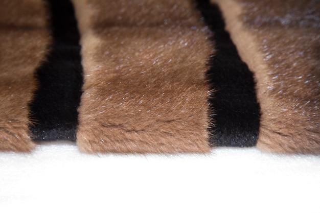Zwarte nertsjas geïsoleerd op een witte achtergrond. luxe natuurlijke vacht. bontjas met capuchon