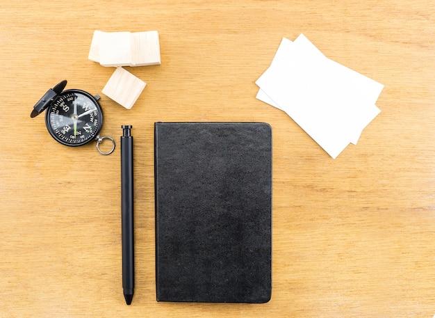 Zwarte notebook, pen, kompas en visitekaartje op houten tafel,